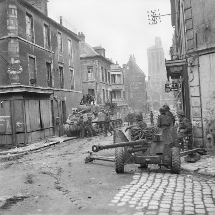 British_Sherman_tanks_and_a_6-pdr_anti-tank_gun_in_the_centre_of_Caen,_Normandy,_10_July_1944__B6924.jpg
